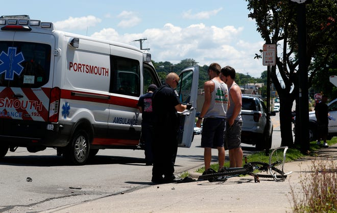"""Lancaster Police Officer Adam Dilley, left, talks to people at the scene of a crash Friday afternoon, June 21, 2019, on East Main Street just near Cherry Street in Lancaster. Dilley said a man on a bicycle was flown to Grant Medical Center after he lost control of the bicycle and while on the sidewalk and entered the lanes of traffic. The man made contact with a pickup, but Dilley said it wasn't immediately clear if bicycle ran into the truck or if it was ridden in front of the truck. Lancaster Fire Department Asst. Chief K.J. Watts said the man was conscious at the scene """"but showing of a head injury"""" and """"other multiple injuries"""" including internal injuries. The bicyclist was taken to Air Evac Lifeteam base at the Pleasant Township Fire Department station on Coonpath Road by Lancaster firefighters before he was flown to Grant."""