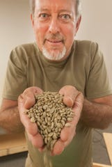 South African native Robin Mountain holds up green coffee beans in the Ntaba Coffee Haus on Brownsboro Road in Louisville. Ntaba translates to mountain in Zulu. Mountain came to the U.S. in July, 20 years ago. He has a successful African Safari tour company which he will run out of the cafe which includes coffees imported directly from African countries. 21 June 2019