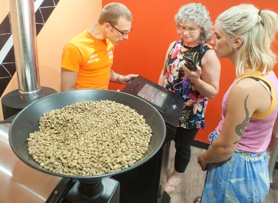 The loading pan of the Ntaba Coffee Haus's new coffee roaster. Learning how to use a new computerized coffee roaster from Brett Potter, AGK, Inc. technician, left, is owner Robin Mountain's wife, Stella, and assistant manager Devon Gray, right. AGK is an automatic coffee roaster industrial electronic contractor. 21 June 2019