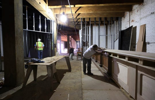 John Hayes inspects his work on a bar inside the Louisville Throughbred Society under construction in the Hughes Lofts.