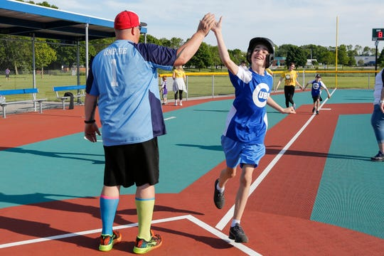 Chase VanMaastricht, 14, of Sheboygan, high fives the umpire as he crosses to home plate during a game at Miracles Park Thursday, June 20, 2019, in Manitowoc, Wis. Miracle League of the Lakeshore is in its sixth season with 10 teams, 100 players and more than 100 volunteers. Joshua Clark/USA TODAY NETWORK-Wisconsin
