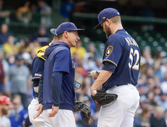 Brewers manager Craig Counsell has a few words with starting pitcher Jimmy Nelson in the first inning when the right-hander allowed three runs against the Reds on two hits with a pair of walks and a hit batter.