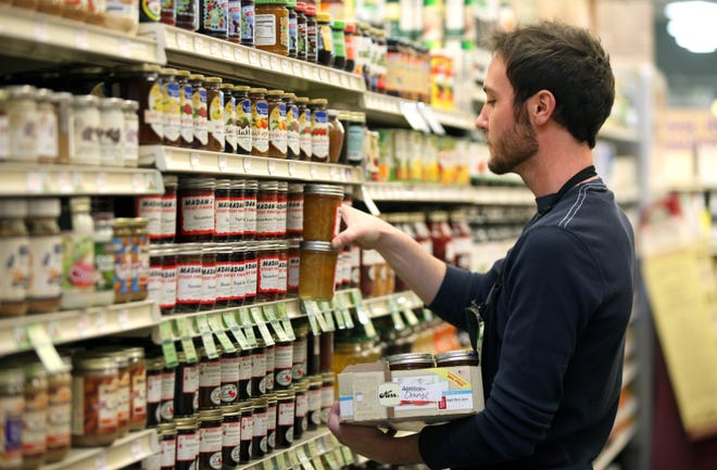 Luke Maurer, grocery journey person, is stocking jam and jelly at Outpost Natural Foods in Wauwatosa in this file photo from December 2013. The store has recently begun a $1.2 million expansion and remodel.