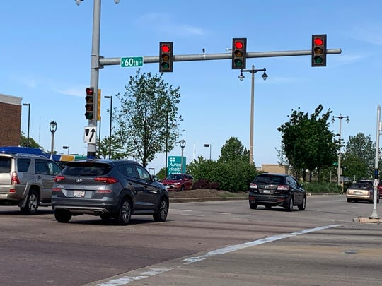 Vehicles race through the red light at West Capitol Drive and North 60th Street on June 20, two days after Milwaukee Police Officer Kou Her was killed at this intersection on his way home by a driver accused of blowing through the traffic signal.