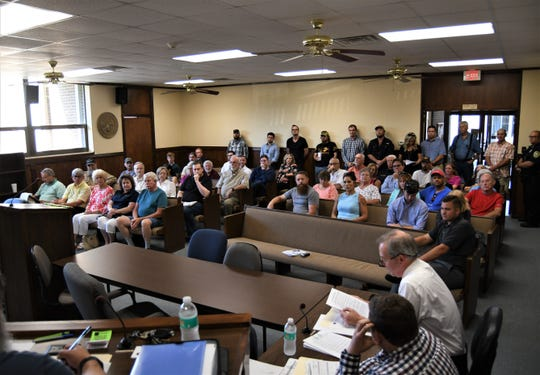 A crowd of more than 40 people listen Thursday night as Mountain Home City Attorney Roger Morgan reads a proposed ordinance that would create a downtown entertainment district.