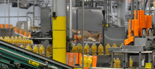 Orange juice bottles move through the production lines at Whitfield Foods. The plant announced an expansion last year.
