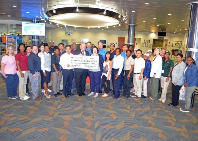 Hyundai Motor Manufacturing Alabama employees present a donation Thursday to the Montgomery Area Food Bank at the plant.