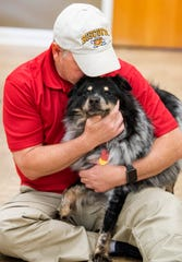 Spooky the dog gets a hug fromt Denton Hawk at the Montgomery Humane Society offices in Montgomery, Ala., on Friday June 21, 2019. Spooky is a long term rehab dog who now resides in the offices at the shelter.