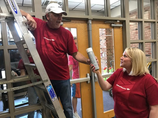 Jaime Settles and Ashley Mullins of Bank of America clean the windows of the lobby at Poplar Grove School on June 21, 2019.