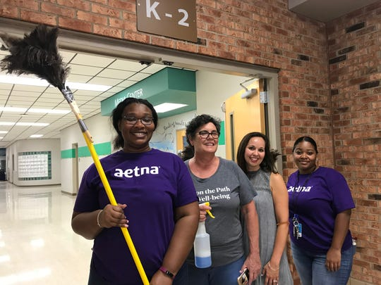 Volunteers from corporate partner Aetna — Mailon Ridley, left, Suzanne Sanders and Mikka Parrish, far right — and principal Alisha Erickson, second from right, complete the dusting at Poplar Grove Elementary School.