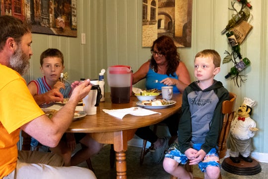 John and Tricia Sewell, alongside their boys Jacob and Abel, eat dinner at their home Monday, June 17, 2019, in Chattanooga, Tenn. The Sewell boys were abruptly cut from state insurance last year, forcing their parents to pay out of pocket for their medical expenses.