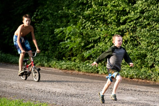 Abel Sewell, 6, runs down the street as Jacob, 13, rides the bike behind him at their home Monday, June 17, 2019, in Chattanooga, Tenn. The boys are among  220,000 Tennessee children who lost or were slated to lose state insurance due to lacking paperwork in recent years.