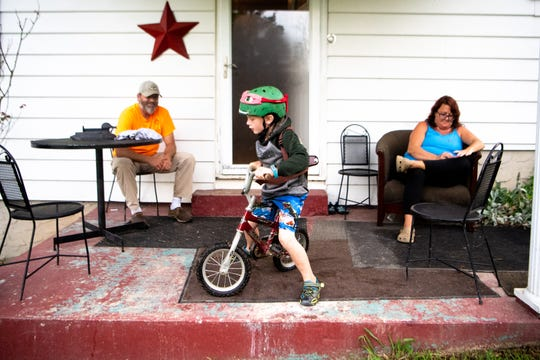 John and Tricia Sewell sit on the front porch as Abel, 6, rides his bike at their home June 17, 2019, in Chattanooga. Abel was covered by TennCare insurance for years, but his coverage vanished in the fall of 2018.