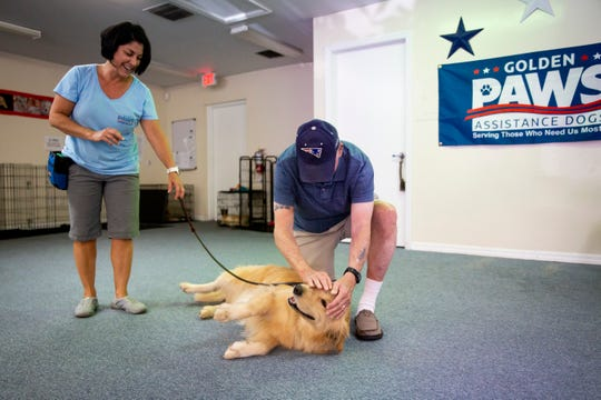 Senior handler JoAnn Agostinelli, left, brings Marli out to visit Richard Barry, right, at Golden PAWS Assistance Dogs in Naples on Thursday, June 20, 2019. Barry, who was a Sgt. 1st Class in the Army Special Forces during the Vietnam War, experiences symptoms of PTSD including flashbacks and nightmares and has been matched with Marli, who will serve as his emotional support animal.