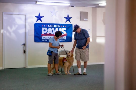 Senior handler JoAnn Agostinelli, left, brings Marli out to visit Richard Barry, right, at Golden PAWS Assistance Dogs in Naples on Thursday, June 20, 2019.