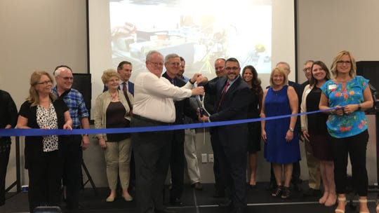 Newark mayor Jeff Hall and Jason Umstot, superintendent/CEO of the Licking County Department of  Developmental Disabilities, cut the ribbon Thursday for the re-dedication of the E.S. Weiant Center.