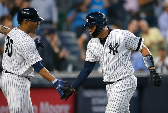 New York Yankees designated hitter Edwin Encarnacion (30) greets catcher Gary Sanchez (24) after hitting a home run in the fourth inning against the Houston Astros at Yankee Stadium.