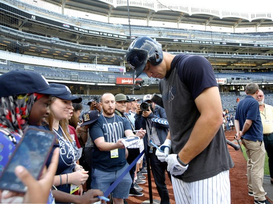 New York Yankees' Aaron Judge signs autographs for fans after taking batting practice before a baseball game against the Houston Astros, Friday, June 21, 2019, in New York.