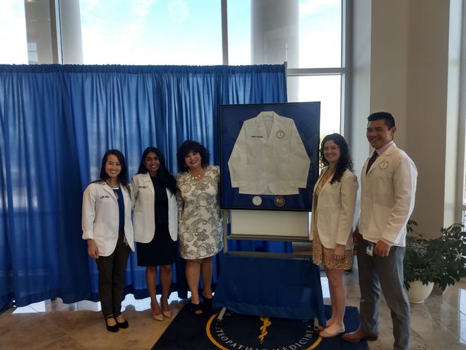 """House Majority Whip Representative Doreen Gallegos from House District 52 in Doña Ana County was presented with a """"white coat"""" by students from the Burrell College of Osteopathic  Medicine for her work in the New Mexico Legislature."""
