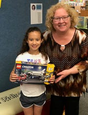 Aunisti receives her prize from Mrs. Nieman at the library.