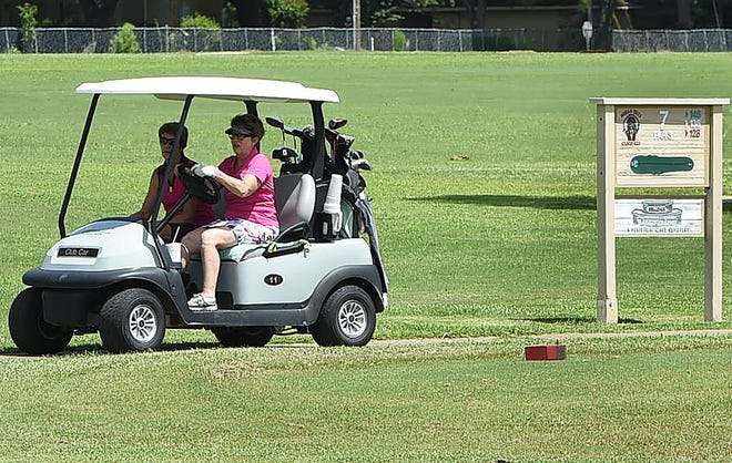 Two golfers travel along a cart path at the Indian Hills Country Club during a women's tournament last week. The club has been listed for $1.8 million, and may close if it doesn't find a buyer.