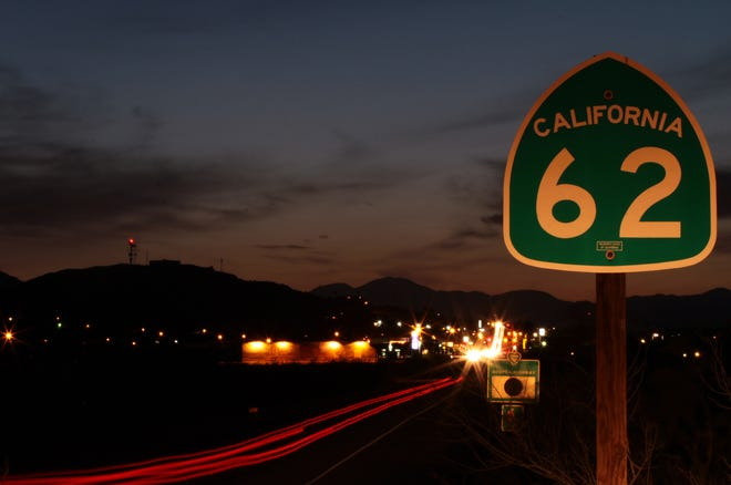 Traffic travels along Highway 62 east of downtown Twentynine Palms, creating streaks of headlights and taillights at sundown.