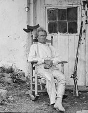 "John Burns, the ""old hero of Gettysburg,"" with gun and crutches taken at his Gettysburg house shortly after the battle."
