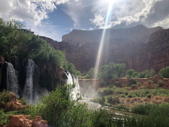 A beam of sun penetrates the clouds at Navajo Falls.