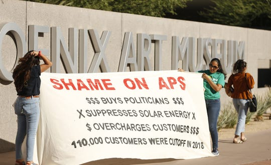 Protestors put up a banner during a protest outside of the Phoenix Art Museum where the Arizona Chamber of Commerce and Industry awards ceremony celebrating Don Brandt, CEO of Arizona Public Service in Phoenix, Ariz. on June 20, 2019.
