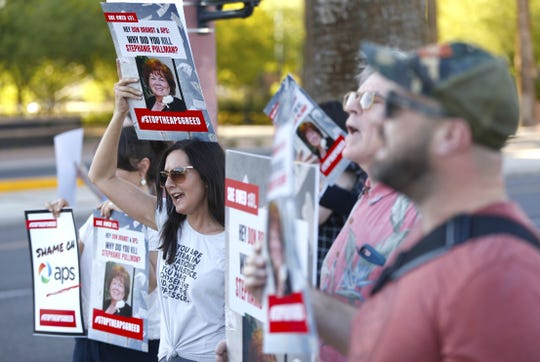 Stacey Champion (center) holds up a sign with Stephanie Pullman's picture during a protest outside of the Phoenix Art Museum where the Arizona Chamber of Commerce and Industry awards ceremony celebrated Don Brandt, CEO of Arizona Public Service in Phoenix, Ariz. on June 20, 2019. Pullman died in her home after her electricity had been shut off.