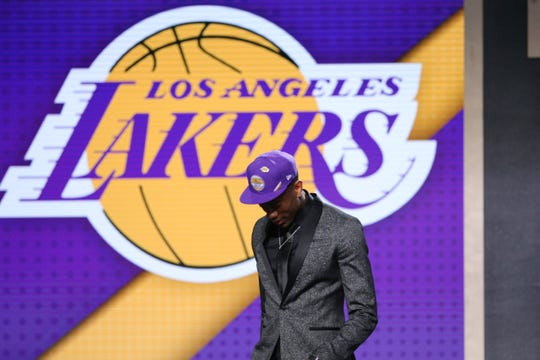 Virginia's De'Andre Hunter walks across the NBA draft stage under a Lakers banner with a Lakers hat on, despite the fact he's headed to the Pelicans.