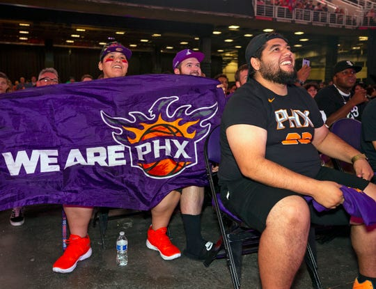 Suns fans Maria Vasquez England and Xavier England, back left, and Erik Arambula, front right, react after hearing the Suns' selection of Cameron Johnson out of North Carolina.