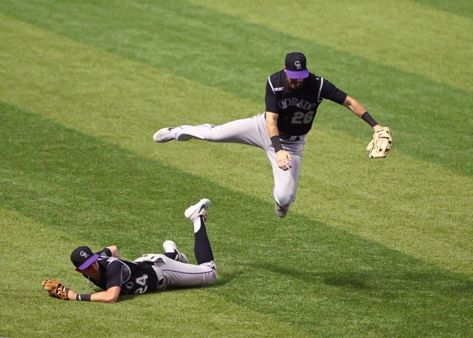 Jun 20, 2019; Phoenix, AZ, USA; Colorado Rockies outfielder David Dahl (right) leaps over teammate Ryan McMahon while trying to field a fly ball in the tenth inning against the Arizona Diamondbacks at Chase Field. Mandatory Credit: Mark J. Rebilas-USA TODAY Sports