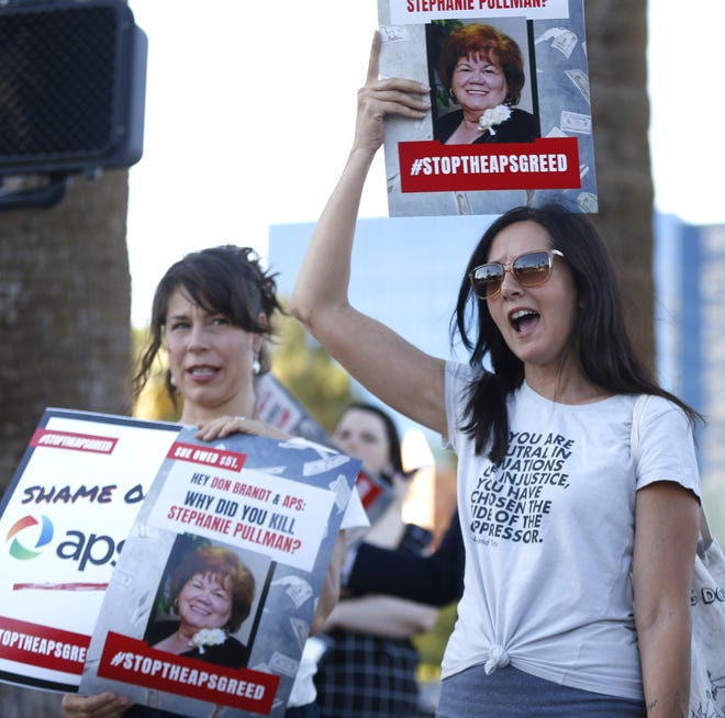 Stacey Champion (right) holds up a sign with Stephanie Pullman's picture during a protest outside of the Phoenix Art Museum where the Arizona Chamber of Commerce and Industry awards ceremony celebrated Don Brandt, CEO of Arizona Public Service in Phoenix, Ariz. on June 20, 2019. Pullman died in her home after her electricity had been shut off.