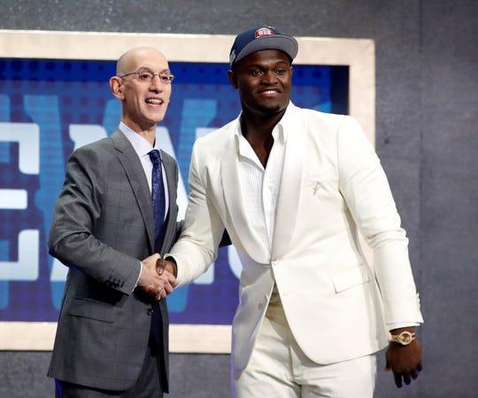 El comisionado de la NBA Adam Silver (i) da la mano al primer seleccionado por los New Orleands Pelicans, Zion Williamson (d).