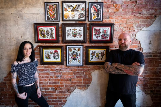 Brian and Nicole Lariccia pose with artwork in the lobby of All Rise Tattoo Friday, June 21, 2019. The husband and wife team opened the tattoo parlor at 916 Military Street in downtown Port Huron.