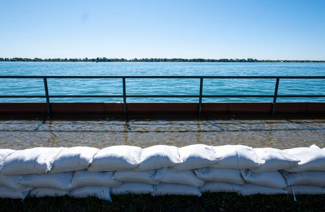 Sandbags are used to contain flooding on a public walkway in Marine City Friday, June 21, 2019.