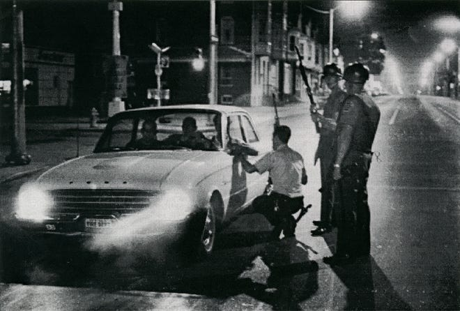Police warn volunteer firefighters not to respond to a fire because of a sniper during the riots of 1969.