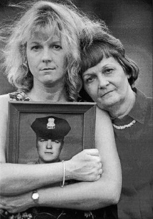 Sharon Schaad, left, holding a picture of her father Henry,  poses with her mother and Henry's widow, Sonja Gilmore. Jason Plotkin photo