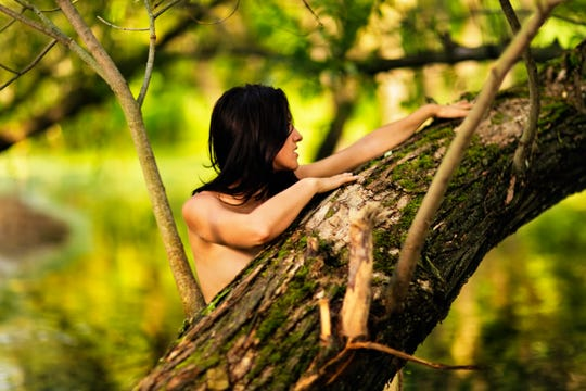 Stock image of a woman behind a tree.