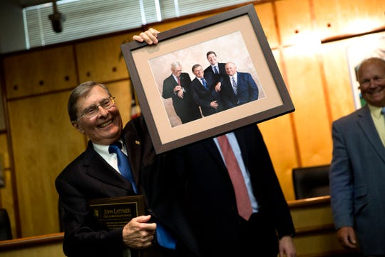 Marion County Chief Administrative Officer John Lattimer holds up a photo of him and the other commissioners during his retirement party at Courthouse Square in Salem on June 20, 2019. Lattimer is retiring at end of this month after 16 years with Marion County and 51 years in public service and government.