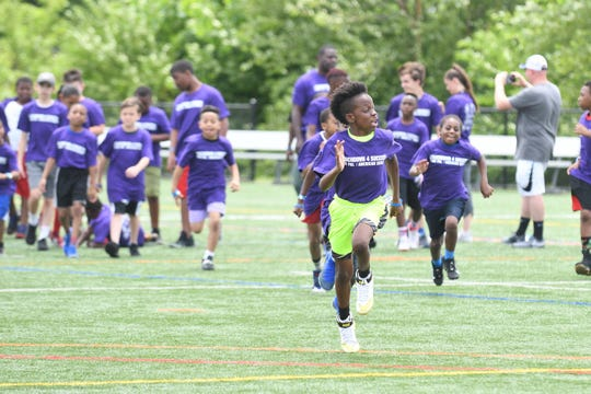 PAL Kids (Police Athletic League) work through football drills at the Salisbury University Intramural fields on Friday, June 21, 2019 with former NFL stars.