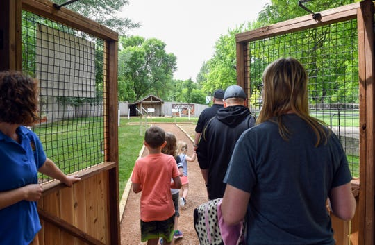 Families enter the kangaroo and wallaby exhibit to walk amongst the animals in the Great Plains Zoo's new interactive Walkabout Australia series Friday, June 21, in Sioux Falls.