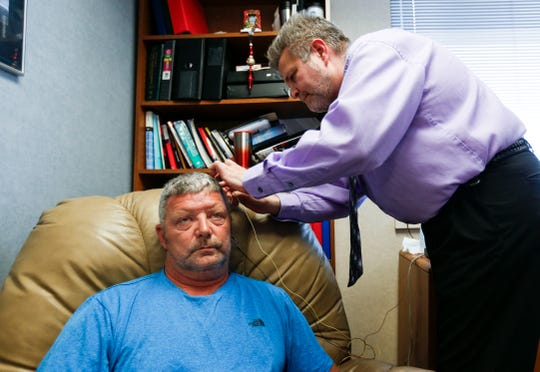 Dr. John Kreymer, a clinical health psychologist at Mercy, affixes electrodes to Andrew Sinclair's head to measure brain signals as part of a neurofeedback treatment to treat pain on Wednesday, June 5, 2019.