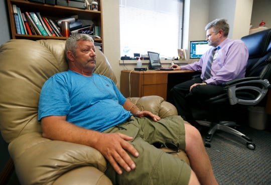 Dr. John Kreymer, a clinical health psychologist at Mercy, monitors brain signals from Andrew Sinclair's head during a neurofeedback treatment to treat pain on Wednesday, June 5, 2019.
