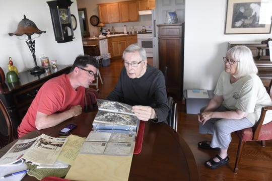 Harold Zosel, 81, flips through his postcard collection with his son, Sam, and wife, Mary, on Thursday, May 20.