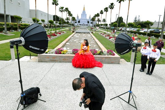 In this Saturday, June 15, 2019 photo, photographer Jose Chavez, of Oakland, looks at a photo on his camera display during a photo session for Quinceanera Dulce Maria Chiquete, of Hayward, at the Mormon Temple garden in Oakland, Calif. Quinceanera is a Latin American Catholic tradition celebrated for girls on or near their 15th birthday. Many have their photo session at the Mormon Temple garden, which has welcomed them for years. (Ray Chavez/San Jose Mercury News via AP)