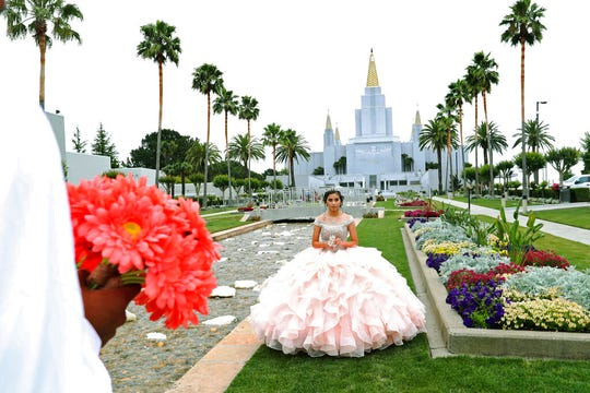 In this Saturday, June 15, 2019 photo, quinceañera  Joseline Garcia, of Oakley, poses during a photo session with photographer Javier Urbina at the Mormon Temple garden in Oakland, Calif. Quinceañeras is a Latin American Catholic tradition celebrated for girls on or near their 15th birthday. Many have their photo session at the Mormon Temple garden, which has welcomed them for years. (Ray Chavez/San Jose Mercury News via AP)