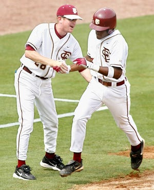 FSU third base coach Mike Martin, Jr.  congratulates Tony Thomas, Jr. as he heads for home after hitting a first-inning three-run home run, to put the Seminoles up 6-0.