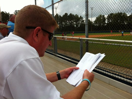 FSU assistant baseball coach Mike Martin Jr. studies a team roster as he attends a summer tournament game.